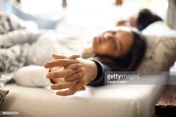 Couple sleeping with holding hands on bed at home