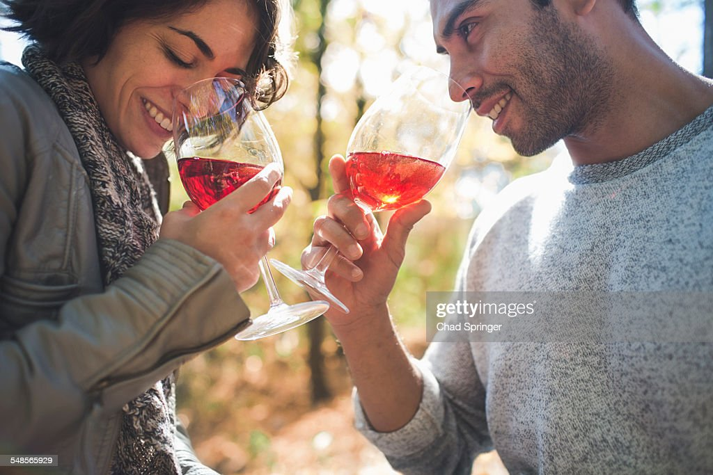 Couple smelling aroma of rose wine in forest : Stock Photo