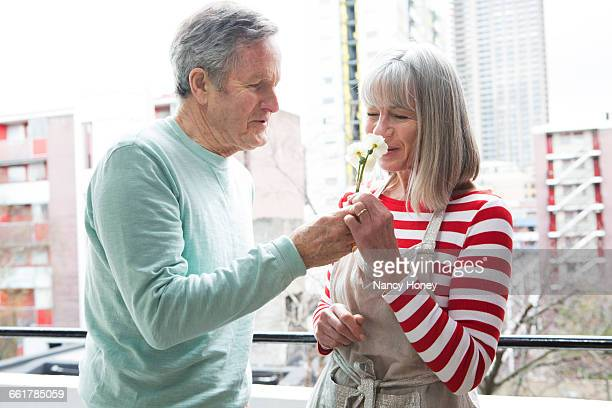 Couple smelling flower on balcony