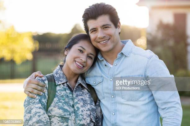couple smile for camera after wife's military tour reunion - military spouse stock pictures, royalty-free photos & images