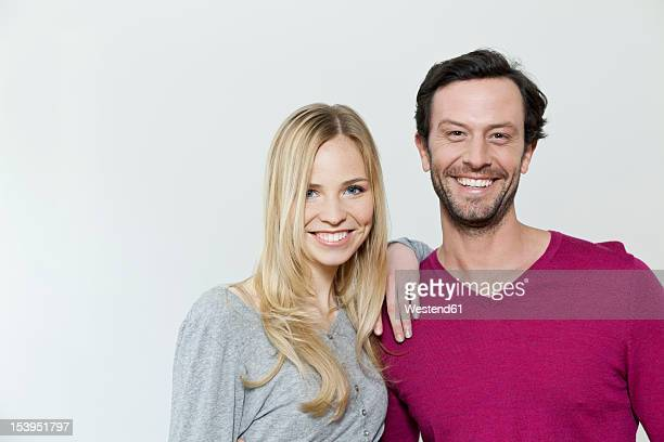 Couple smiling against white background, portrait