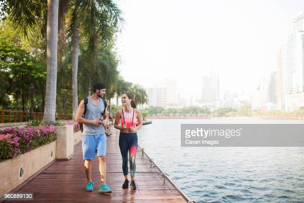 couple smiling and walking on wooden walkway at riverbank - water's edge stock pictures, royalty-free photos & images