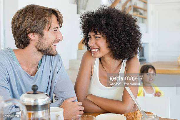 Couple smiling at a dining table with their daughter in the background