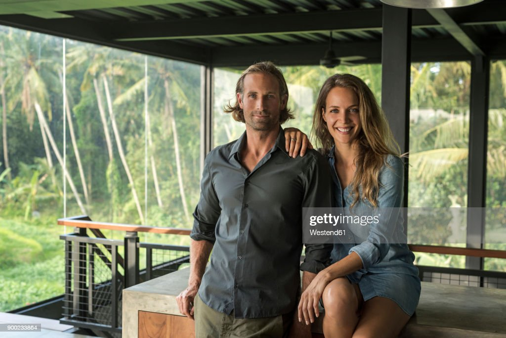 Couple smiling at camera in contemporary design house with glass facade surrounded by lush tropical garden : Stock Photo
