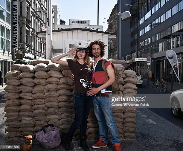 couple smiling at checkpoint charlie - checkpoint charlie stock photos and pictures