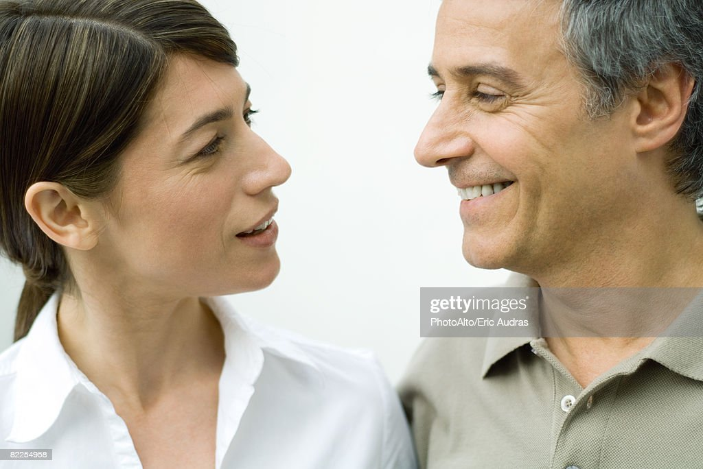 Couple smiling at each other, close-up : Stock Photo