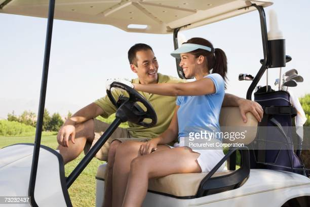 Couple smiling at each other in golf cart