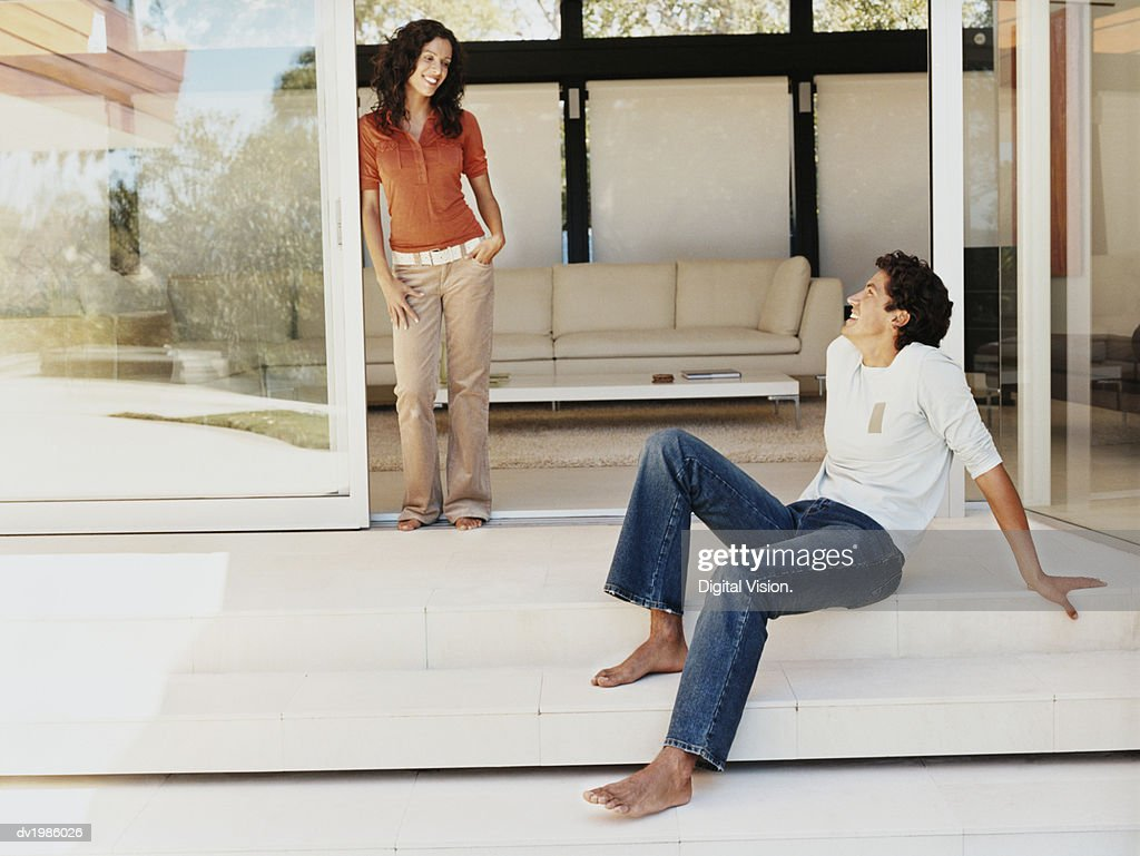 Couple Smiling at Each Other on the Patio of Their Home : Stock Photo