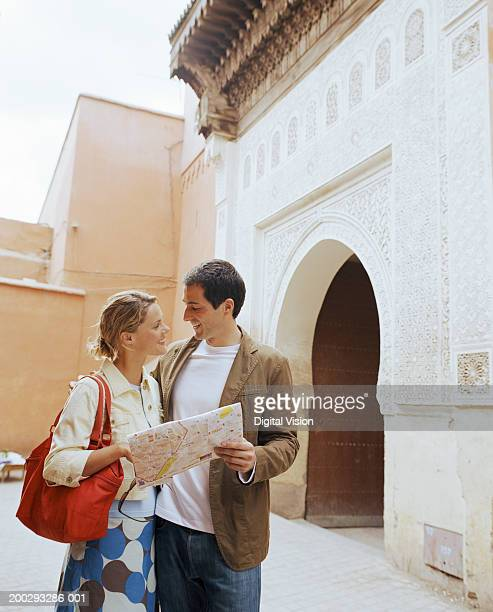Couple smiling at each other outdoors, man holding map