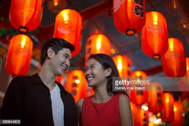 Couple smiling at each other under red lanterns