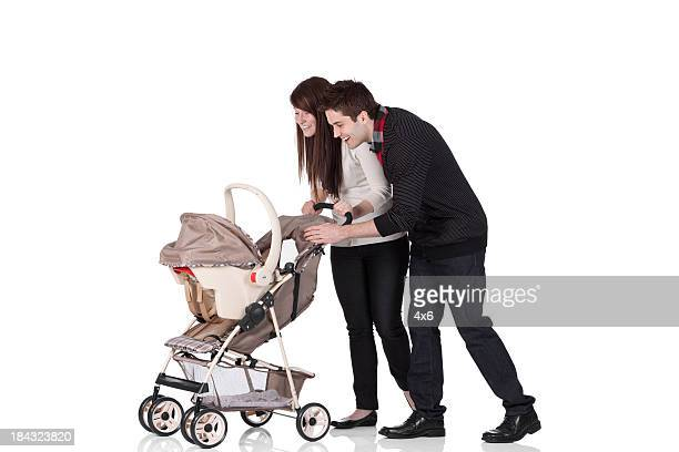 Couple smiling at their baby in a pram
