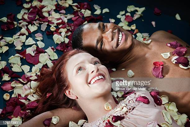 Couple smiling, covered in rosepedals.