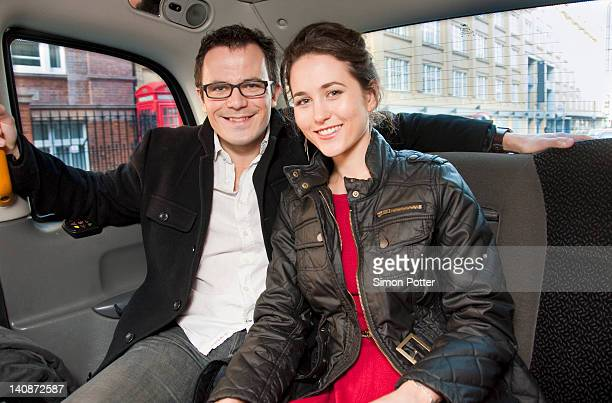 Couple smiling in back seat of car