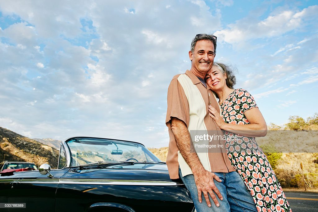 Couple smiling near classic convertible : Foto stock