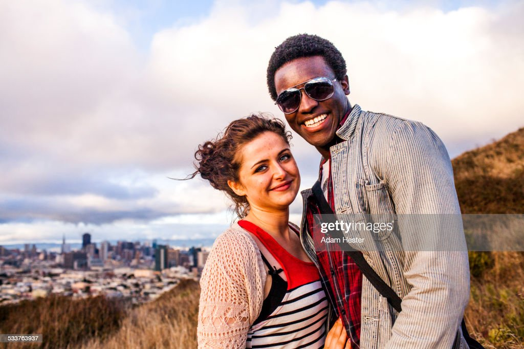 Couple smiling on grassy hill overlooking cityscape : Foto stock