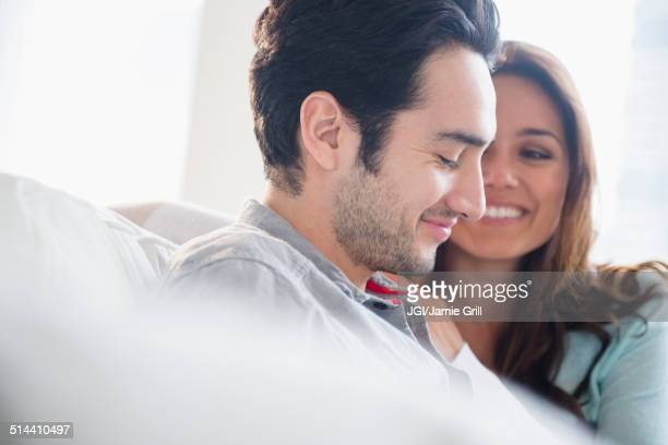 Couple smiling together on sofa