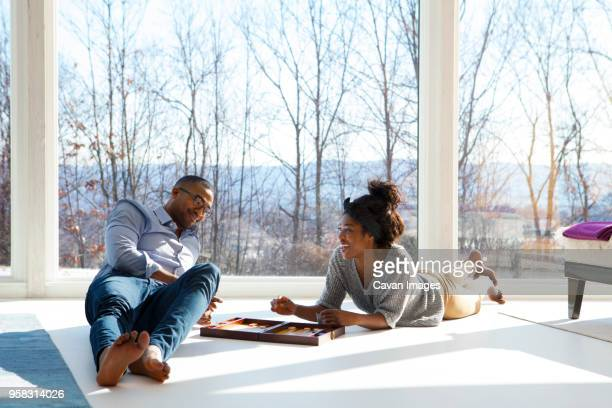 Couple smiling while playing backgammon at home