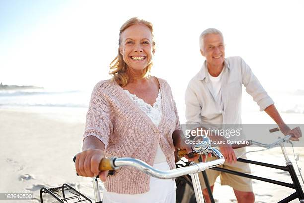 Couple smiling while taking bike ride on beach