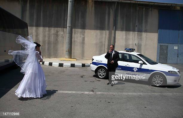 A couple smokes a cigarette next to a Cypriot police car as they wait for the start of a mass civil wedding ceremony for around 100 Israeli and...