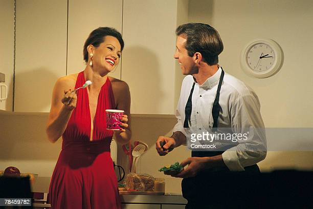 couple snacking at home after a party - kitchen after party stock pictures, royalty-free photos & images