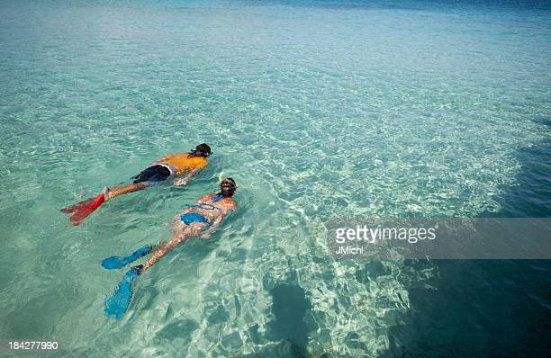 Couple snorkeling in the clear blue Caribbean waters