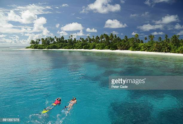 Couple snorkelling towards tropical beach