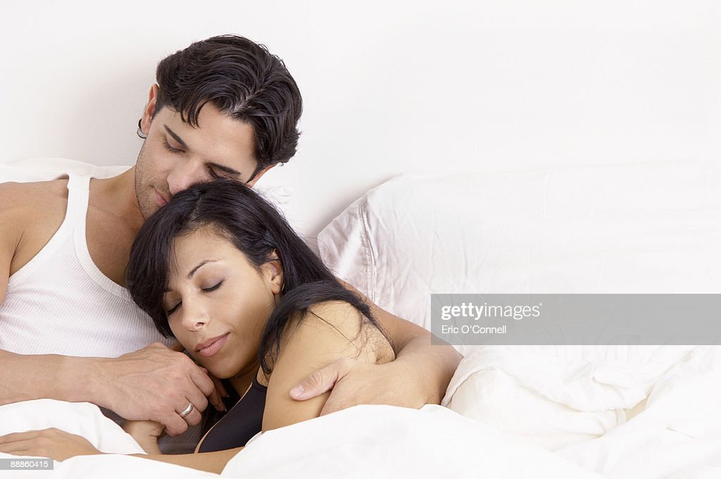 Couple snuggling in bed : Stock Photo