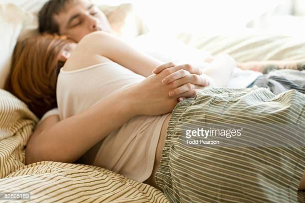 couple snuggling - pareja abrazados cama fotografías e imágenes de stock