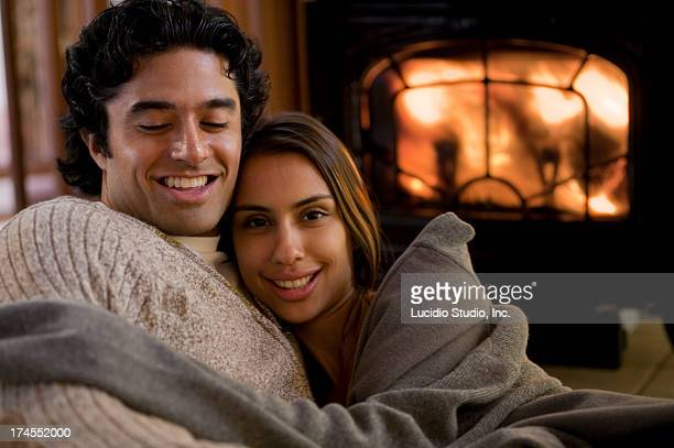 Couple snuggling up by a wood burning stove