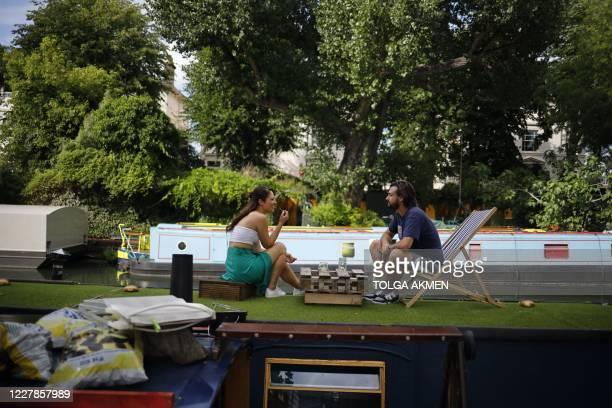 Couple socialise on the roof of a boat in the warm weather on Regent's Canal in London on July 31, 2020. - A storm warning covering much of England...
