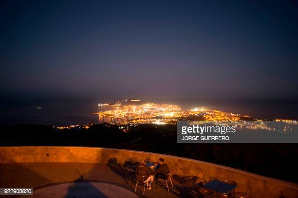 A couple speaks in a terrace bar in the Spanish North African enclave of Ceuta on February 21 2018 / AFP PHOTO / JORGE GUERRERO