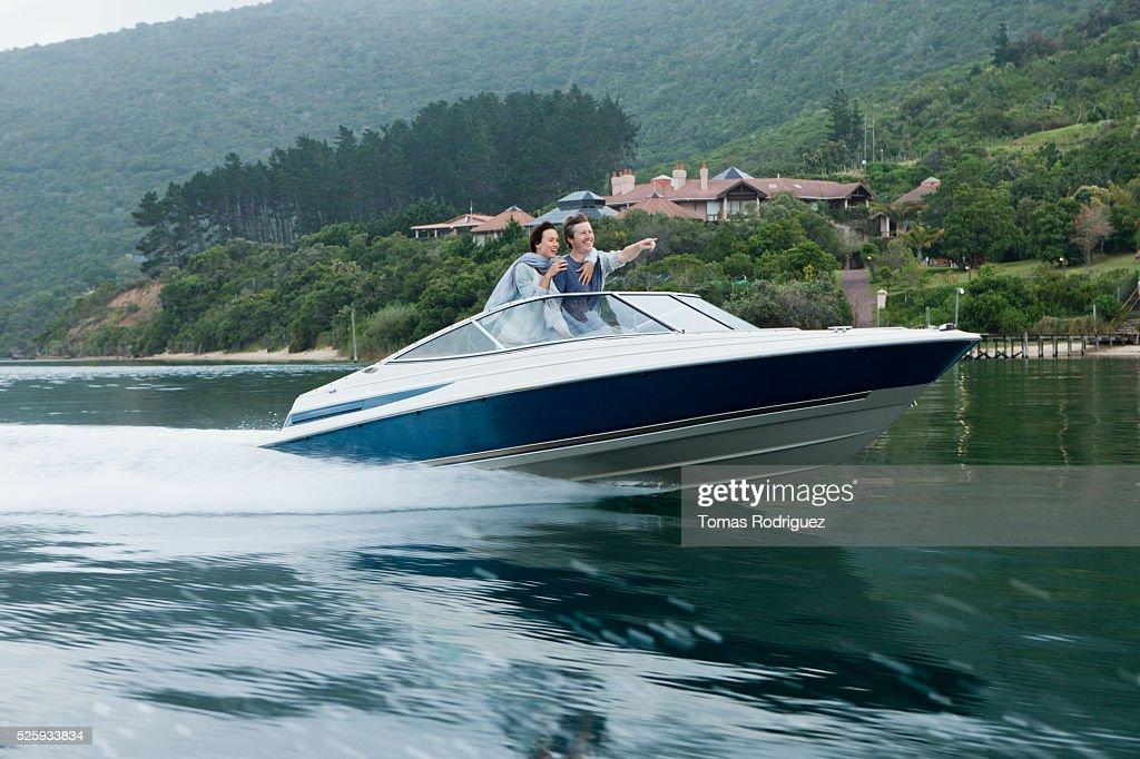 Couple speeding on motorboat : Photo