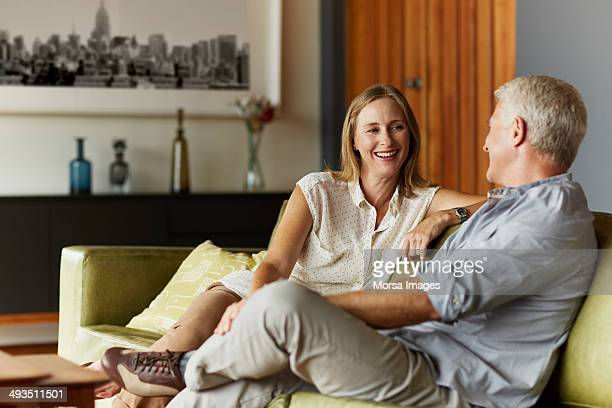 couple spending leisure time in living room - koppel stockfoto's en -beelden