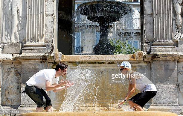 A couple splash each other in a fountain during a heatwave on July 1 2015 in Paris France France is currently experiencing a heatwave which has...