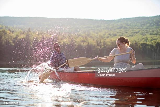 couple splash each other with canoe paddles while boating on lake - solo adulti foto e immagini stock