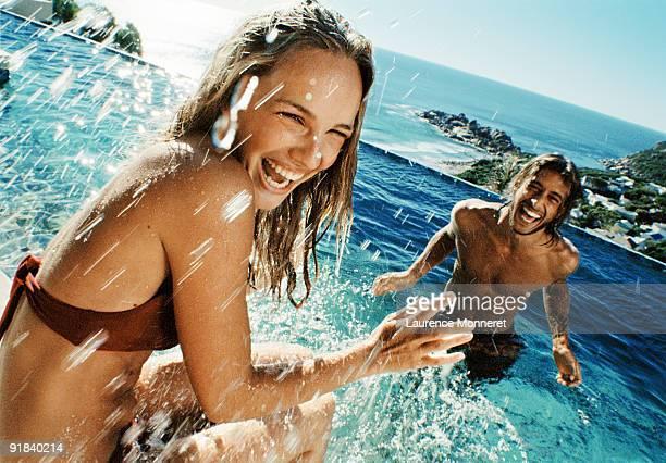 Couple splashing in swimming pool