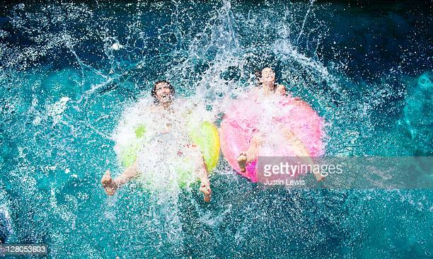 A couple splashing into a pool on inner tubes