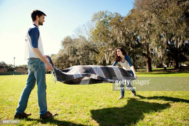 couple spreading blanket on field at park during sunny day - spreading stock pictures, royalty-free photos & images