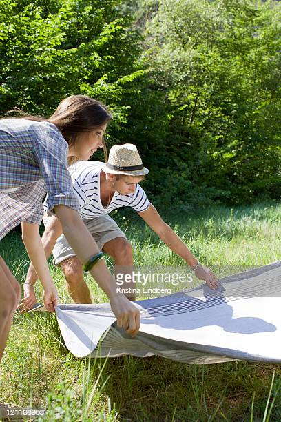 Couple spreading out picnic blanket.
