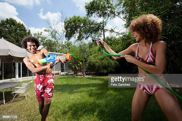 Couple squirting each other with water in backyard