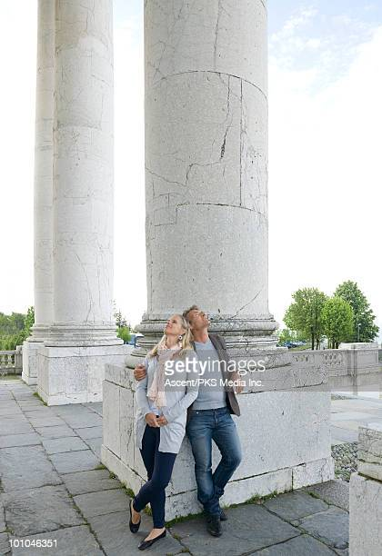 Couple stand at base of marble pillars, looking up