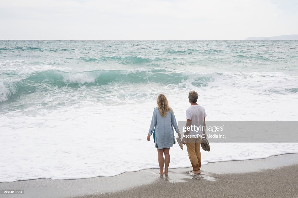 Couple stand at surf's edge, looking out to sea : Stock Photo