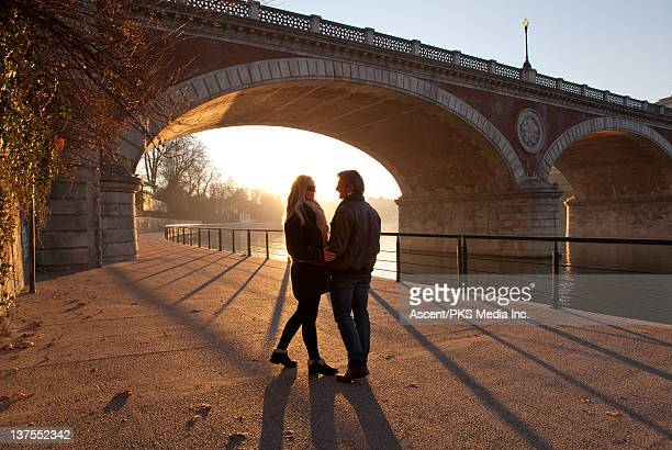 couple stand below stone bridge at sunrise,romance - ponte ad arco foto e immagini stock