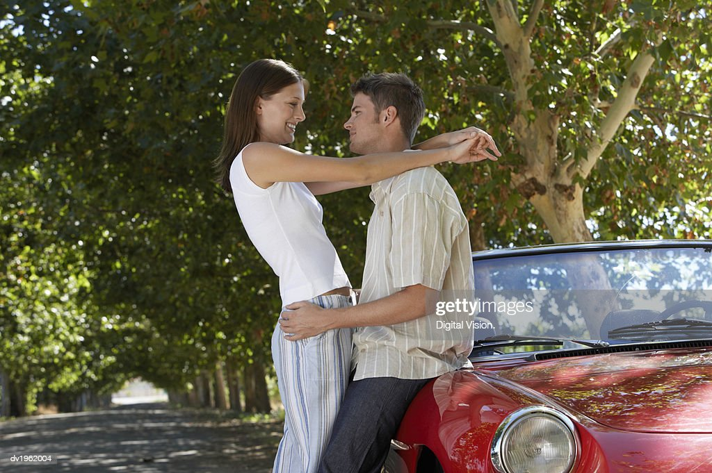 Couple Stand by a Convertible Car, Embracing : Stock Photo