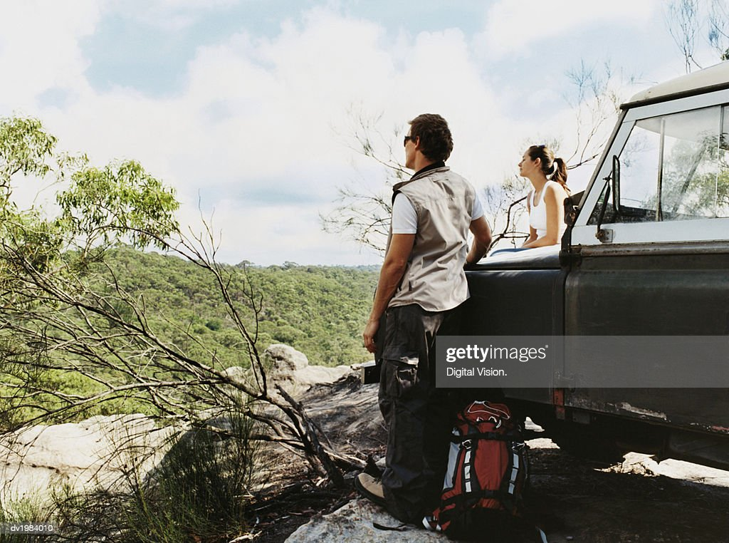 Couple Stand by Their Parked SUV, Looking at the View of the Countryside : Stock Photo