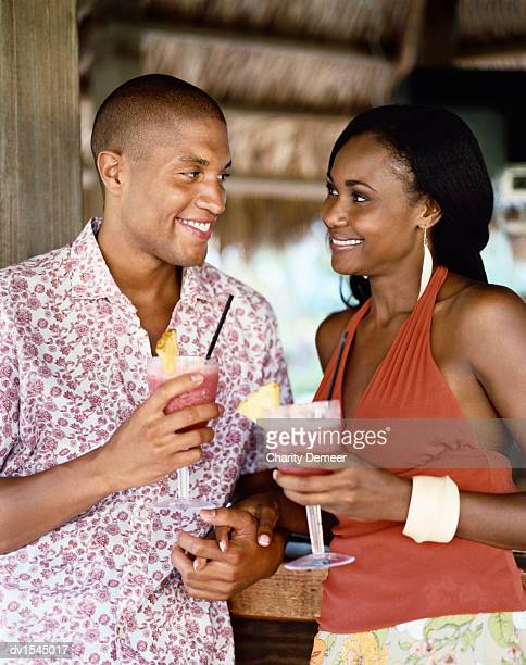 Couple Stand Holding Hands and Leaning on a Bar While Holding Cocktails