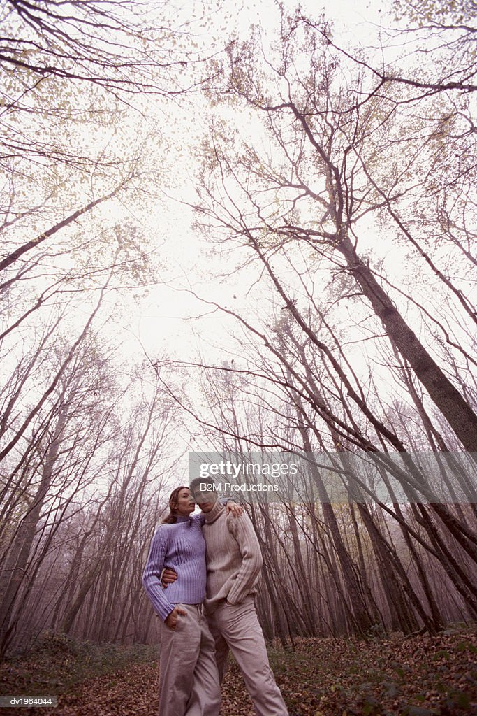 Couple Stand in a Forest With Their Arms Around Each Other Looking at View : Stock Photo