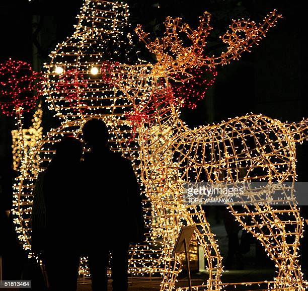 A couple stand in front of an illumination of snowman and reindeer displayed near a department store at Shinzuju business and shopping district in...