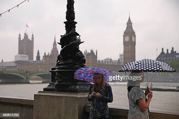 A couple stand in heavy rain on the South Bank on August 13 2015 in London England The Met Office has issued an amber warning for heavy rain in the...