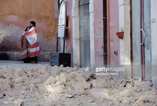 Couple stand in rubble in rubble on April 6, 2009 in the center of the Abruzzo capital L'Aquila, the epicenter of an earthquake measuring...